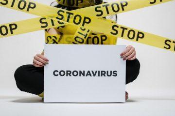 Personne portant un panneau indiqué Coronavirus avec des barrières stop