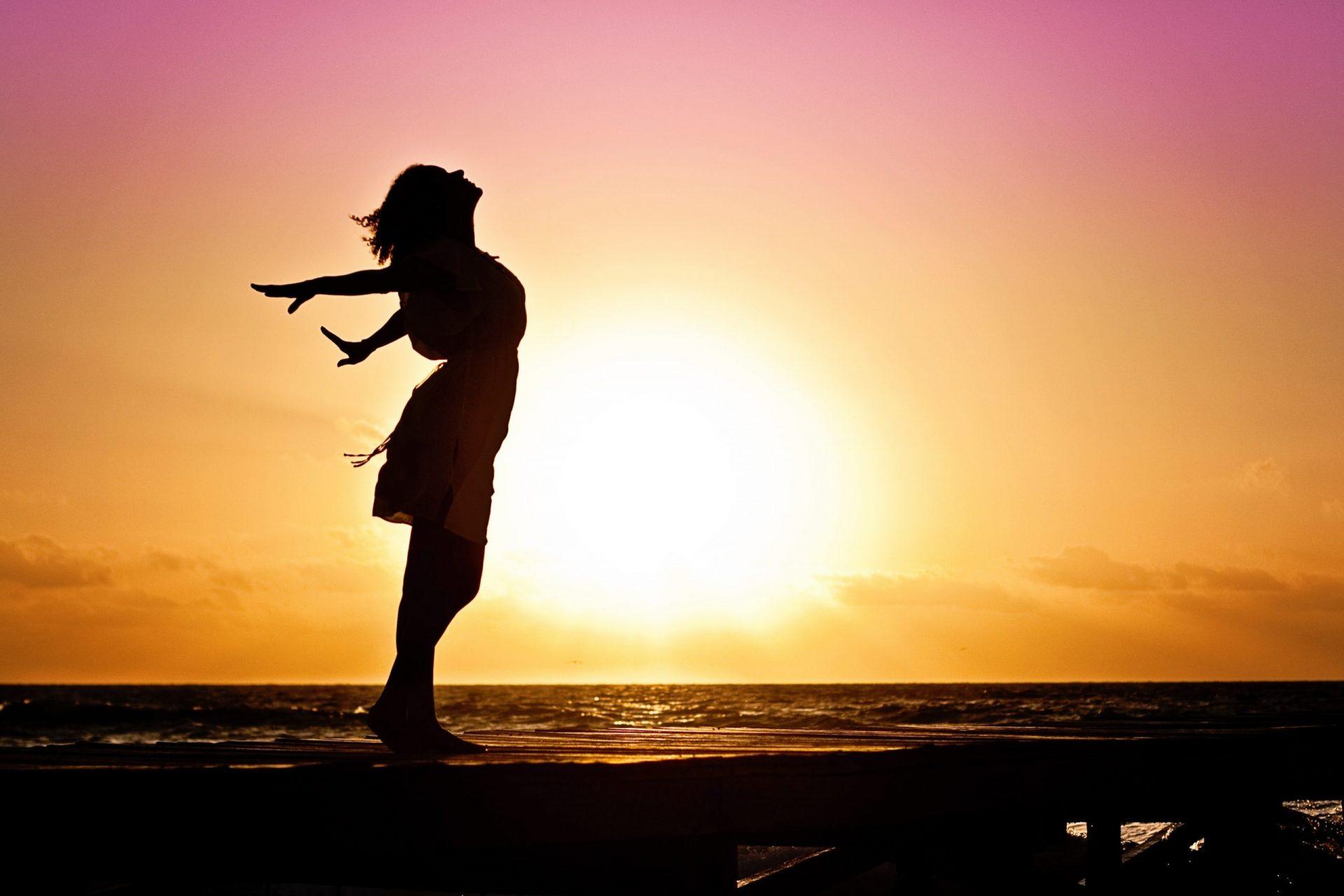 Une silhouette de femme devant un coucher de soleil les bras écartés qui respire