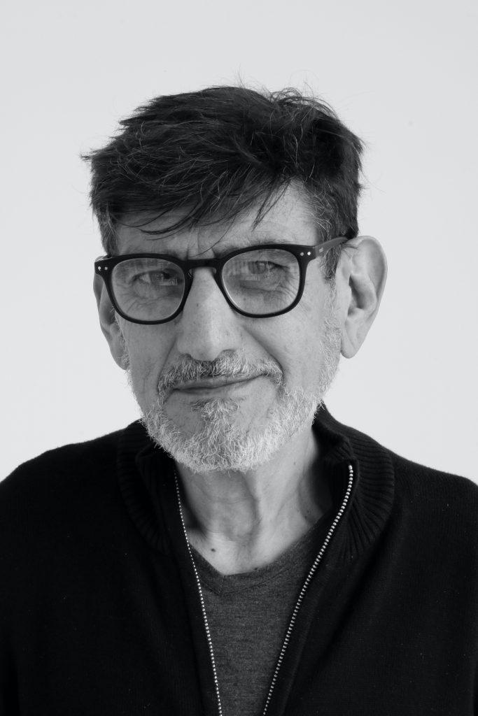 Un homme d'une cinquantaine d'années avec des lunettes et un pull zippé