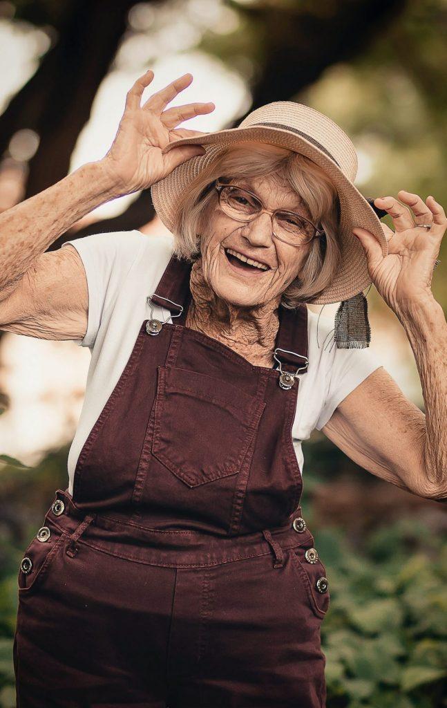 Une dame âgée joyeuse avec un chapeau et une salopette