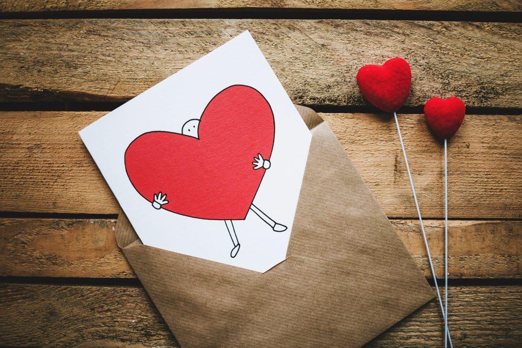 Une enveloppe kraft qui laisse sortir une carte avec un coeur