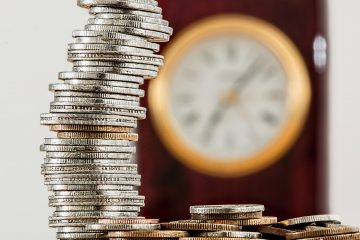 Une pile de pièces devant une horloge floutée